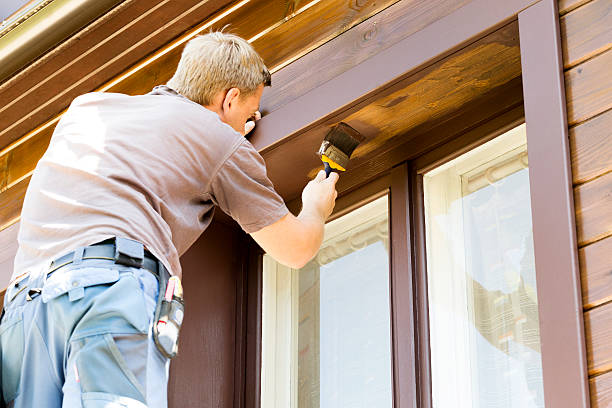 man with paintbrush painting brown wooden house exterior