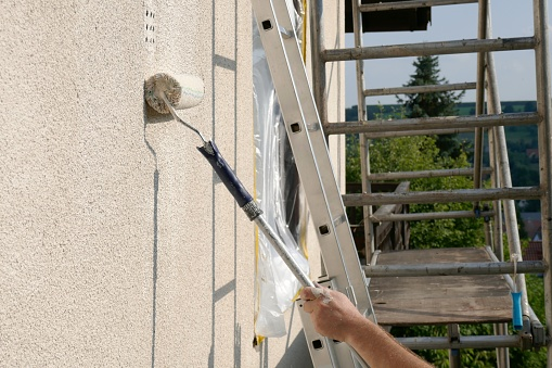 painting walls.Repair and construction concept.Details of painting walls, roller,staircase, scaffolding and other tools for painting walls of the house outside.home renovation outside